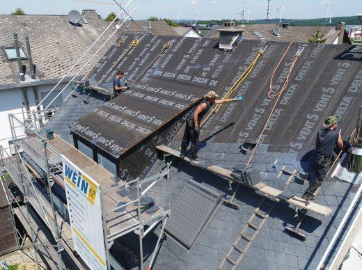 Dachdecker auf Dach beim Dachdecken mit Isolation und Schiefer