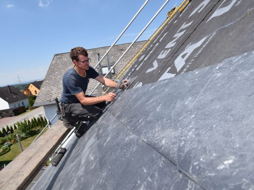 Dachdecker bei der Dachdeckung mit Schiefer