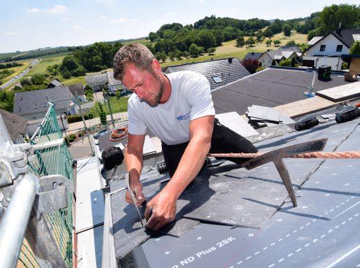 Dachdecker beim Dachdecken mit Schiefer